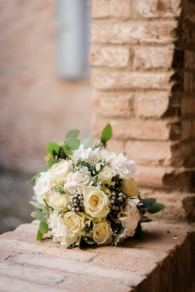 A beautiful and sunny bouquet in yellow and white sits atop an ancient villa wall in Italy shot by luxury wedding photographer Francesco Bognin
