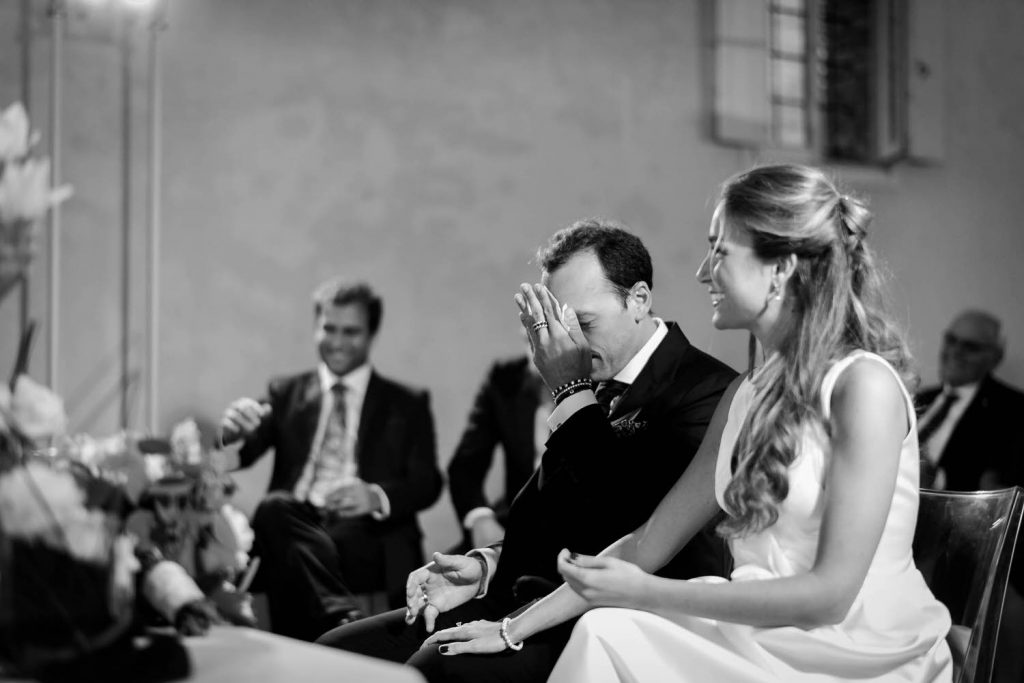 Black and white reportage moment showing a wedding ceremony with smiling witnesses, a smiling bride and very emotional and tearful groom in Italy by luxury wedding photographer Francesco Bognin