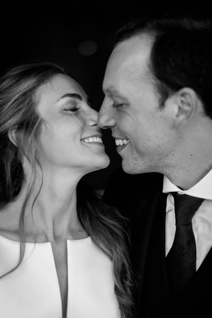 A close up portrait in black and white of a smiling bride and groom in profile just before a kiss in Italy shot by luxury wedding photographer Francesco Bognin