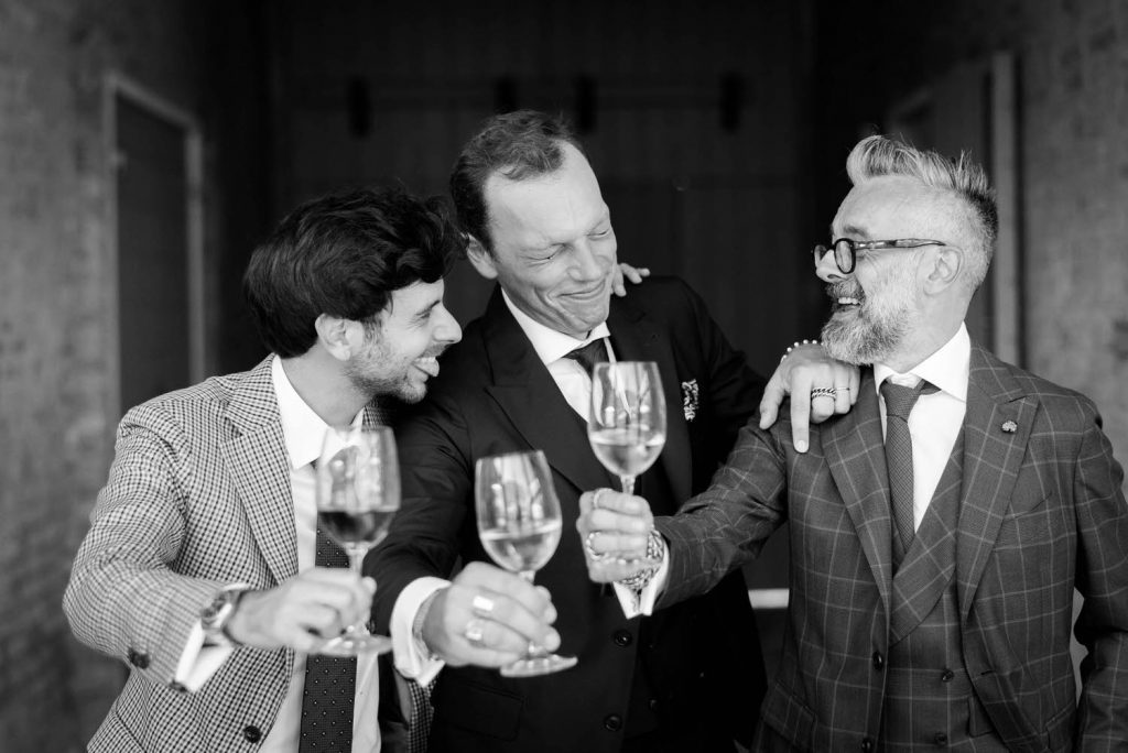 Black and white photo of a groom and two guests enjoying a lively moment as they laugh smile and raise their glasses for a cheers by luxury wedding photographer Francesco Bognin