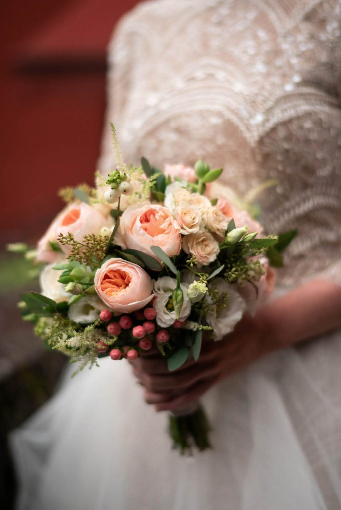 Close up of a beautiful bridal bouquet in pinks and corals against gorgeous beaded and tulle wedding dress in Villa Pizzo Lake Como shot by luxury wedding photographer Francesco Bognin