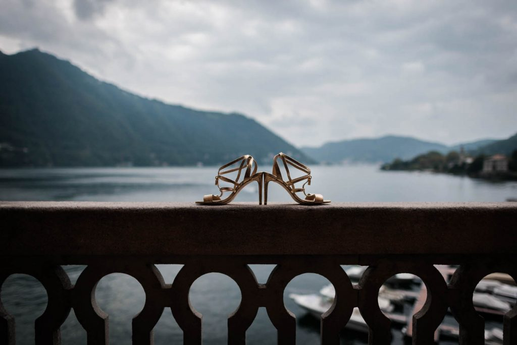 A beautiful pair of golden bridal shoes perch back to back on the balcony wall of Villa Pizzo overlooking the hills and waters of Lake Como in Italy Fine art wedding photography by luxury wedding photographer Francesco Bognin