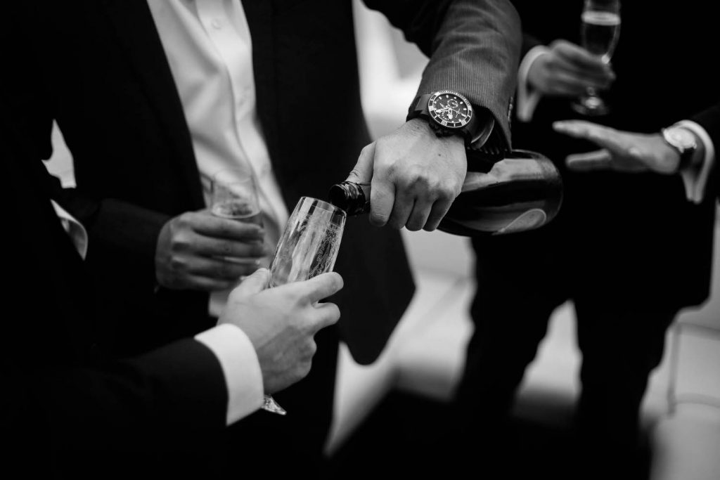Fine art black and white photo showing torsos, hands and arms as champagne is poured by the groom of a wedding on Lake Como at Villa Pizzo in Italy Fine art wedding photography by luxury wedding photographer Francesco Bognin