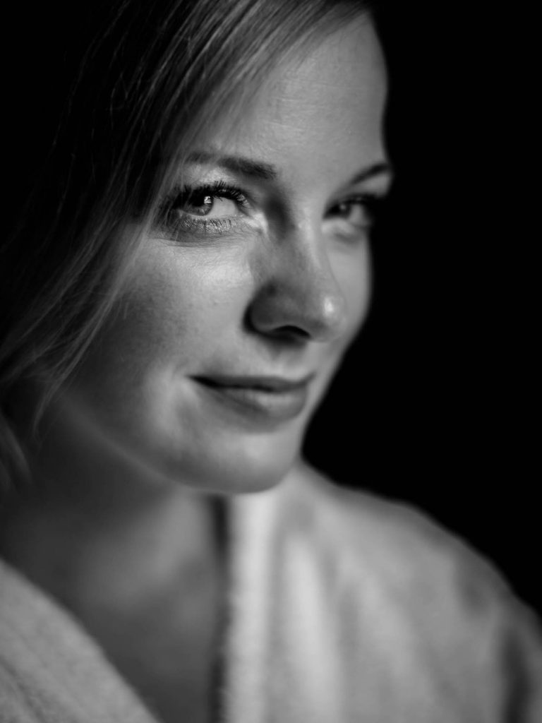 Extreme closeup in black and white of a bride wearing a smile in eyes and a very subtle smile on her lips fine art wedding photography by luxury wedding photographer Francesco Bognin