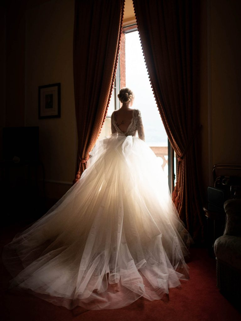 A rich and warm portrait of a bride in her tulle gown standing between drapes and looking out a balcony window toward lake Como at Villa Pizzo in Italy Fine are wedding photography by luxury wedding photographer Francesco Bognin
