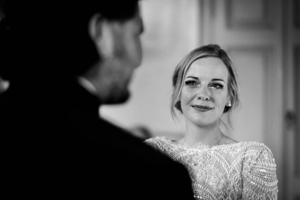 A black and white portrait of a misty eyed bride as seen over the shoulder of her groom at Villa Pizzo at Lake Como in Italy. Fine art wedding photography by luxury wedding photographer Francesco Bognin