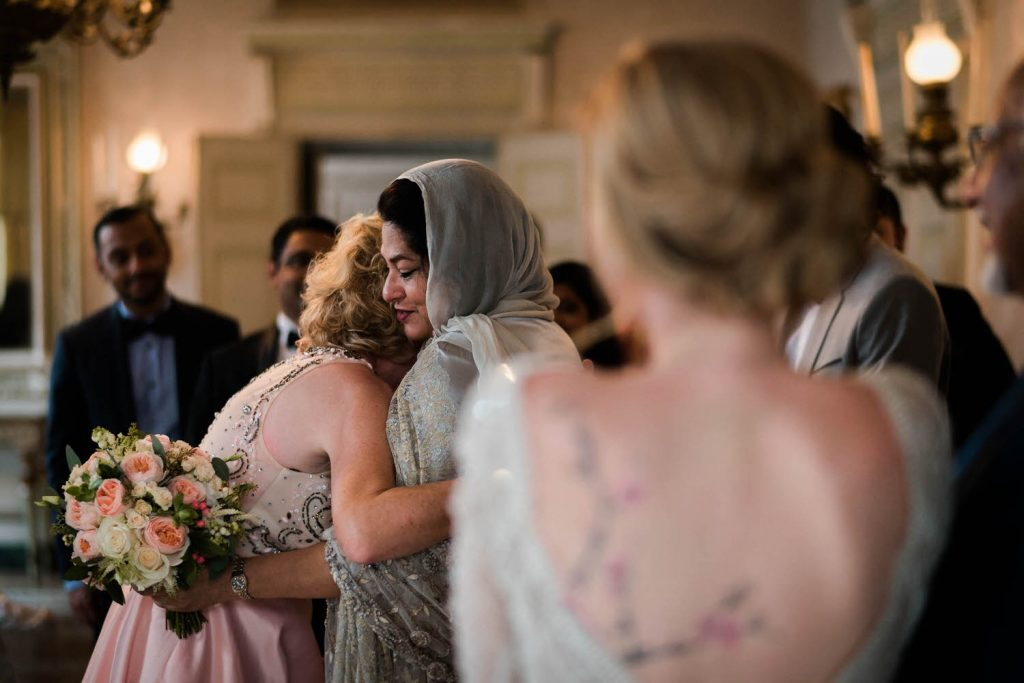 A n emotional embrace between the mothers of the bride and groom, one wearing a headscarf and a look of love and peace all seen from over the shoulder of the bride, wearing a beaded dress that showcases her cherry blossom tattoo that covers her back. Fine art wedding photography by luxury wedding photographer Francesco Bognin