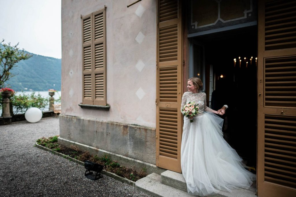 A fine art reportage shot of a bride in motion exiting a door, her dress folliwing behind her as she leaves a beautiful pink and orange building at Villa Pizzo on Lake Como in Italy. Fine art wedding photography by luxury wedding photographer Francesco Bognin