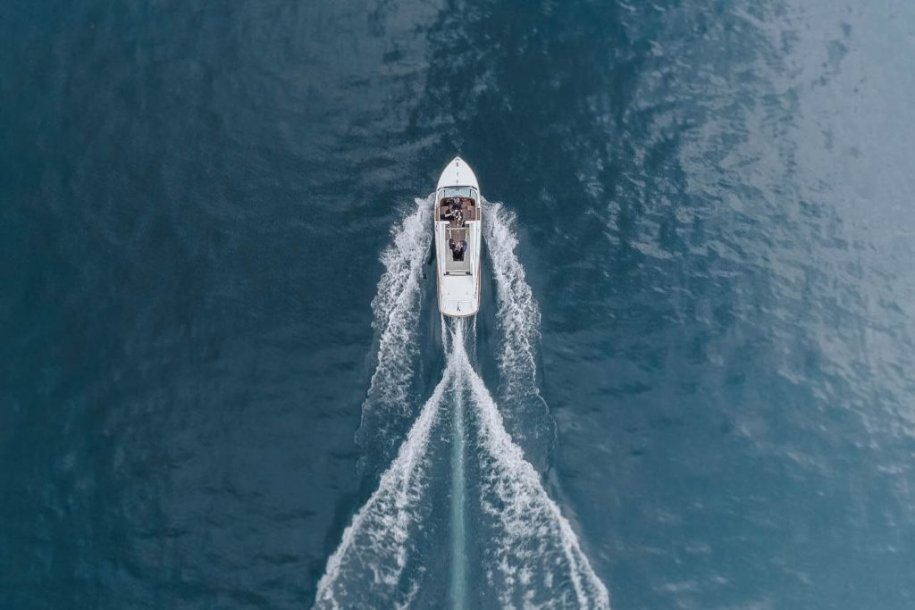 An aerial drone photo from above a boat showing the wake and disturbance of the water in perfect beautiful symmetry on lake Como in Italy. Fine art wedding photography by luxury wedding photographer Francesco Bognin