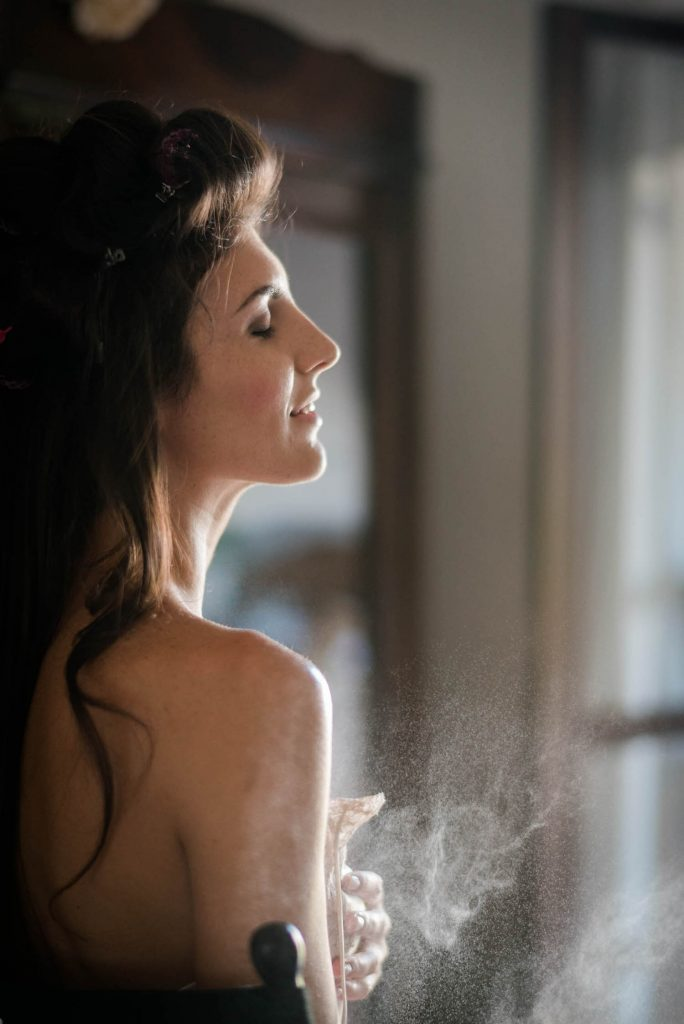 A close up profile of a bride getting ready with her eyes closed as she is misted with a fragrance that is captured in the photo by fine art luxury wedding photographer Francesco Bognin