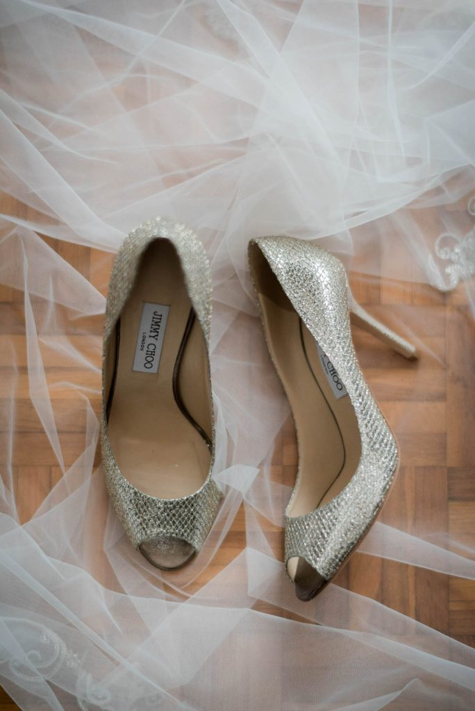 A set of peep toe pumps in metallic sparkle by designer Jimmy Choo sit on a bridal veil over a warm wood floor. Fine art wedding photography by luxury wedding photographer Francesco Bognin