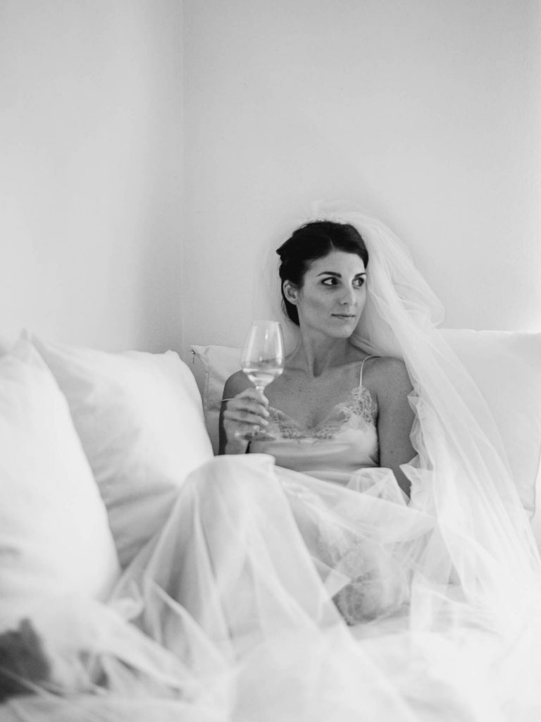 Black and white photo of a bride resting on a couch in her veil and a slip while she holds a glass of whine and looks to her side. Fine art wedding photography by luxury wedding photographer Francesco Bognin