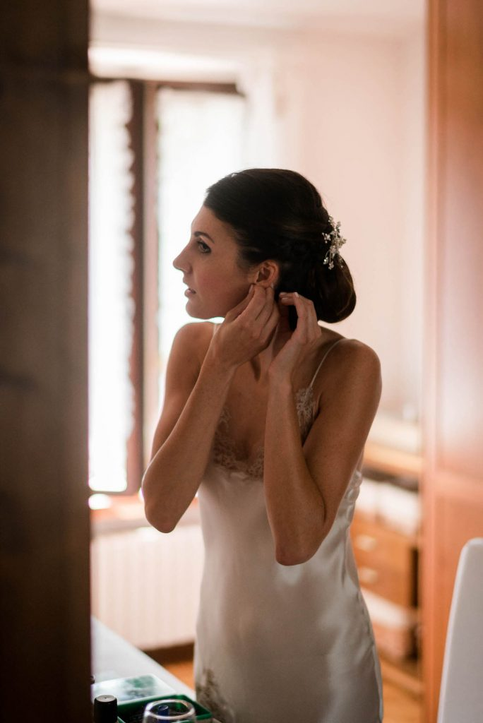 A bride in her slip looks into the mirror and puts on her earrings before the ceremony. Fine art wedding photography by luxury wedding photographer Francesco Bognin