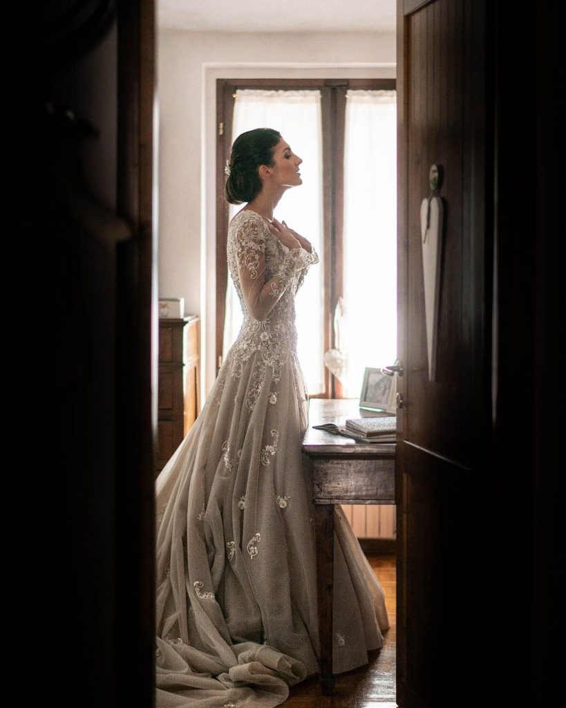 A profile of a bride in her wedding dress looks into the mirror with both hands to her heart before the ceremony. Fine art wedding photography by luxury wedding photographer Francesco Bognin