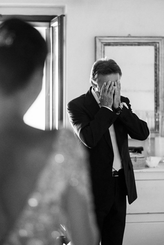 Black and white photo of a man, the father of the bride, holding his face in his hands with emotion after seeing his daughter dressed as the bride before the ceremony. Fine art wedding photo by luxury wedding photographer Francesco Bognin