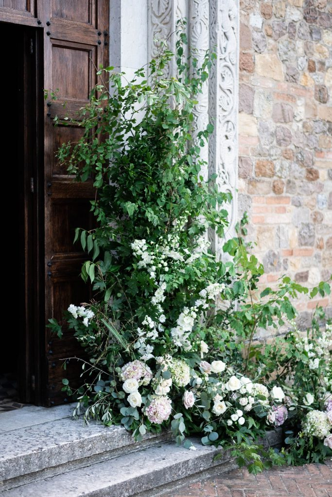 A spectacular Villa door in classic Italian midevil style flannked by gorgeous flowers and greenery in Italy. Fine art wedding photography by luxury wedding photographer Francesco Bognin