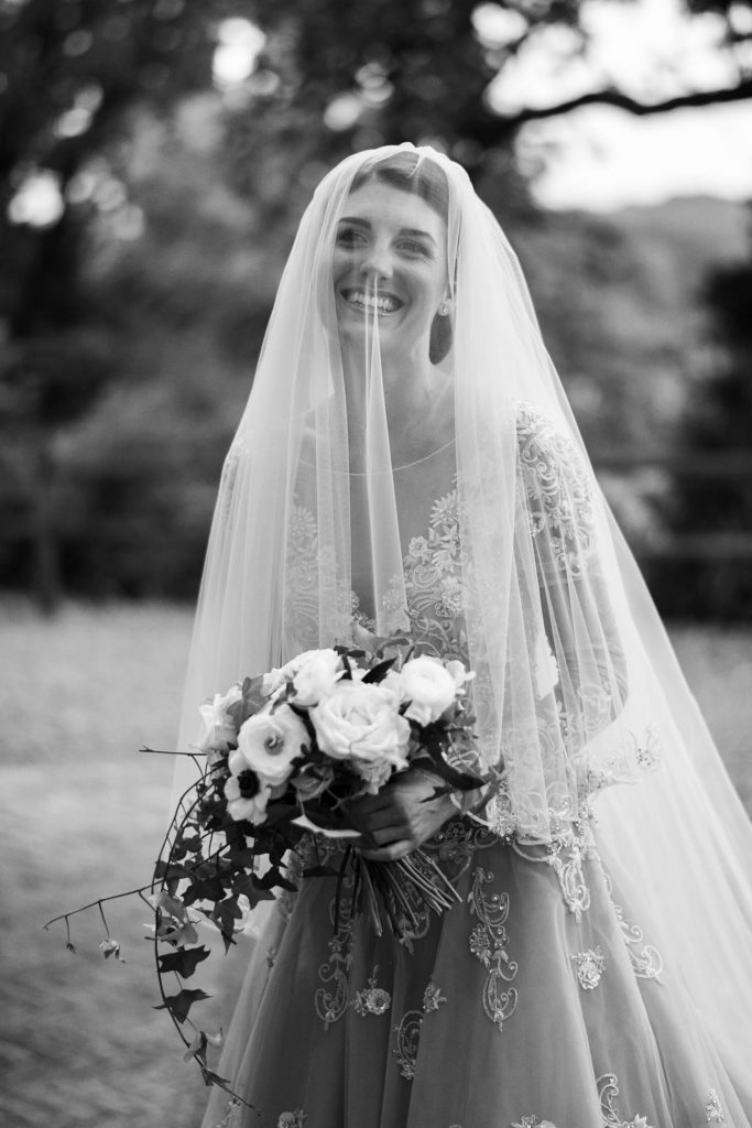Black and white portrait of a smiling bride under her veil and holding her bouquet in an Atelier Eme gown at a castle wedding in Italy. Fine art wedding photography by luxury wedding photographer Francesco Bognin