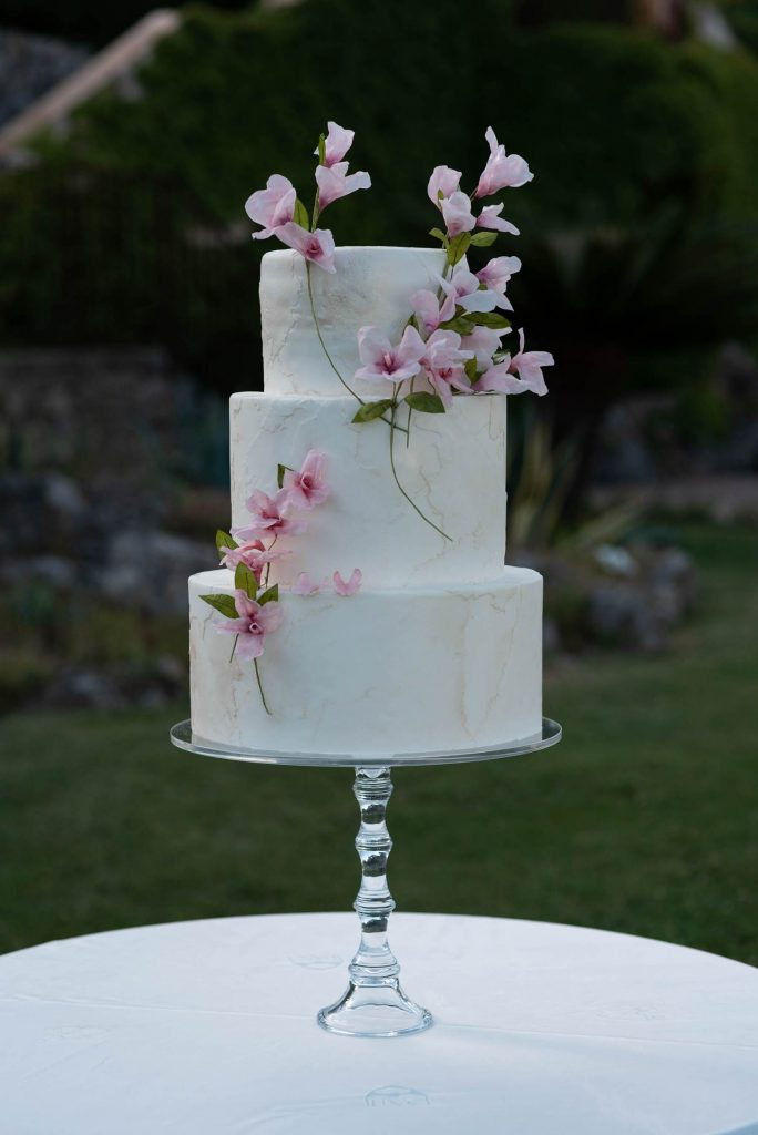 A close up photo of a beautiful three layer wedding cake in textured white, decorated with cherry blossoms and resting on a crystal glass cake stand shot by luxury wedding photographer francesco Bognin