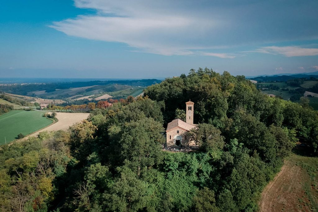An aerial drone photo showing a beautiful castle chapel set among the woods on a hill in Italy with a beautiful blue sky behind. Fine art wedding and drone photography by luxury wedding photographer Francesco Bognin