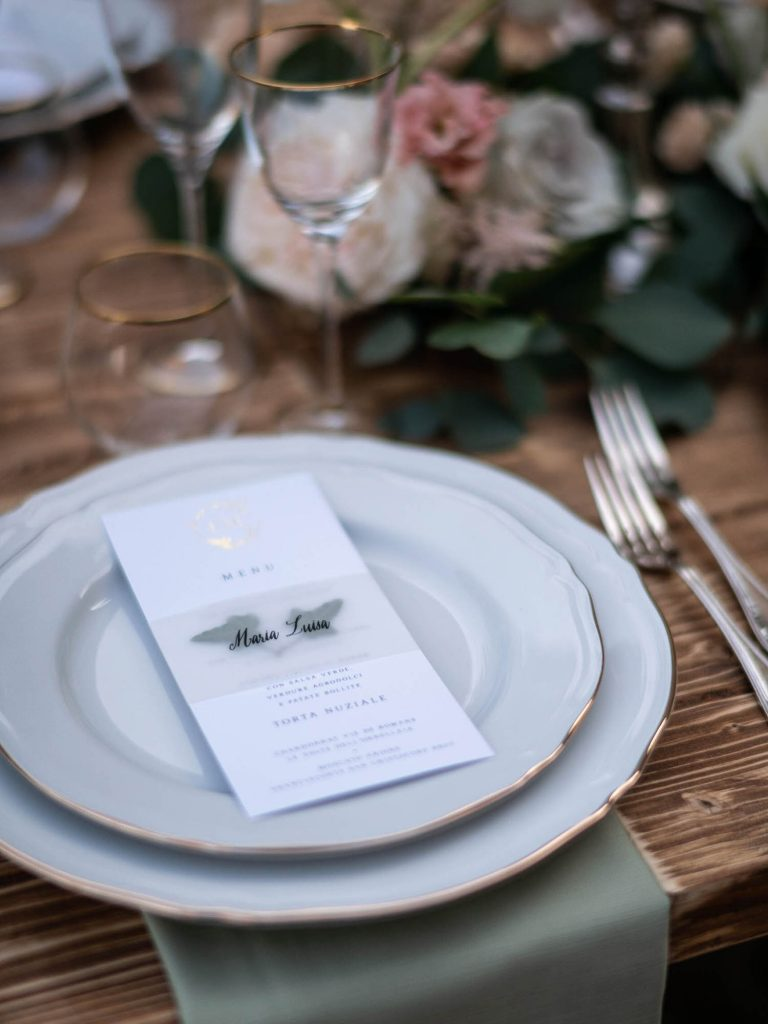 A wedding place setting showing dishes cutlery glassware as well as a menu and flowers. Fine art wedding photography by luxury wedding photographer Francesco Bognin
