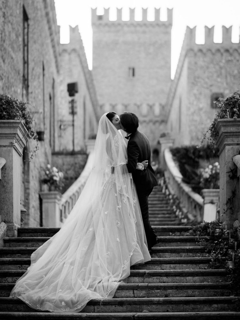 A bride and groom dressed for their wedding share a kiss on the steps of a midevil castle in Italy. Dress by Atelier Eme. Fine art wedding photography by luxury wedding photographer Francesco Bognin