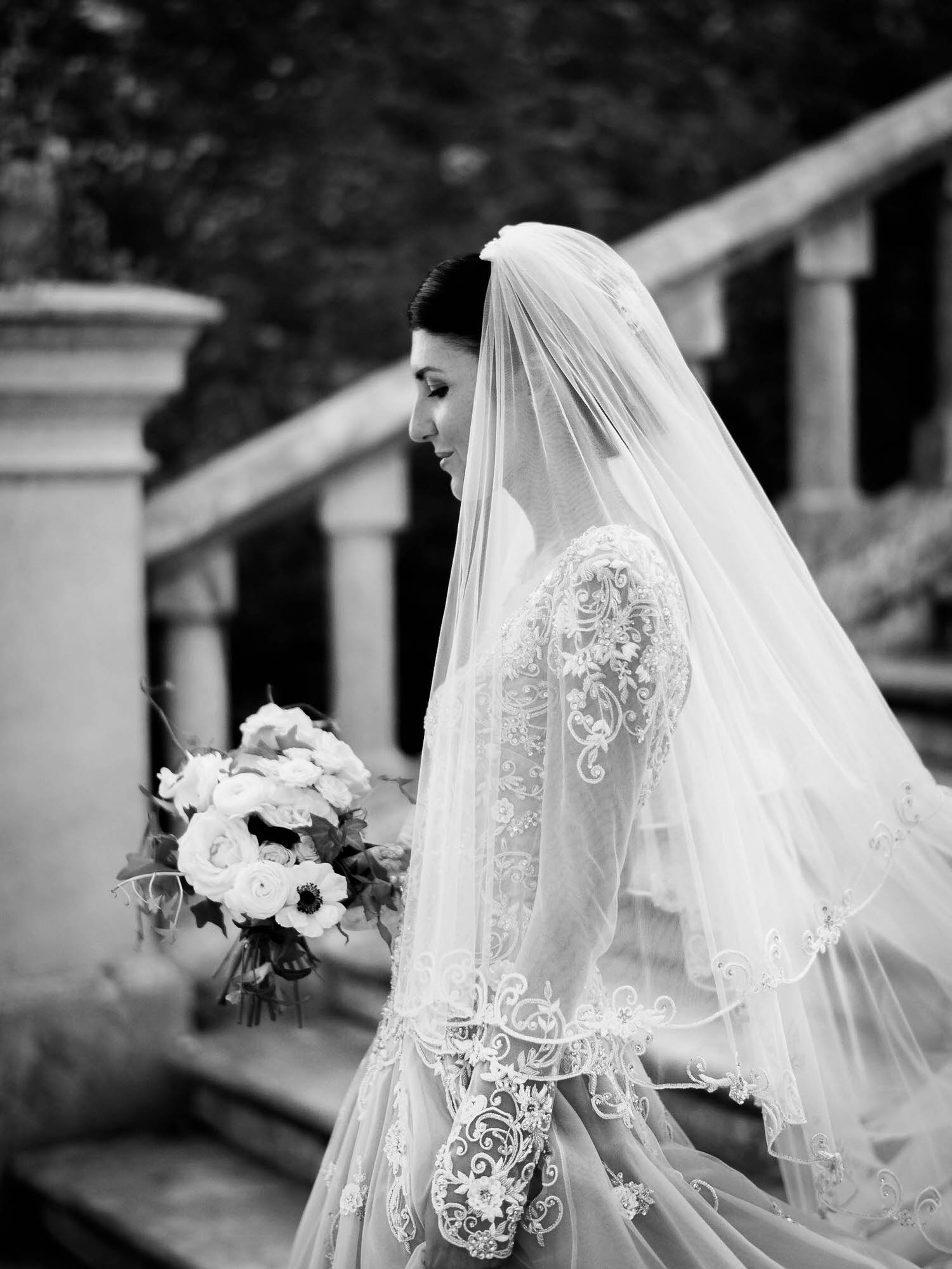 Black and white profile portrait of a gently smiling bride under her veil and holding her bouquet in an Atelier Eme gown at a castle wedding in Italy. Fine art wedding photography by luxury wedding photographer Francesco Bognin