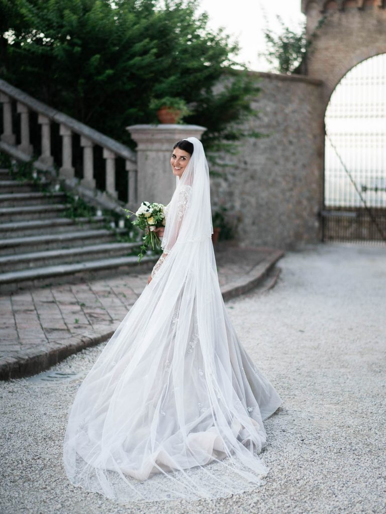 Portrait of a gently smiling bride looking over her shoulder at the camera and holding her bouquet in an Atelier Eme gown at a castle wedding in Italy. Fine art wedding photography by luxury wedding photographer Francesco Bognin