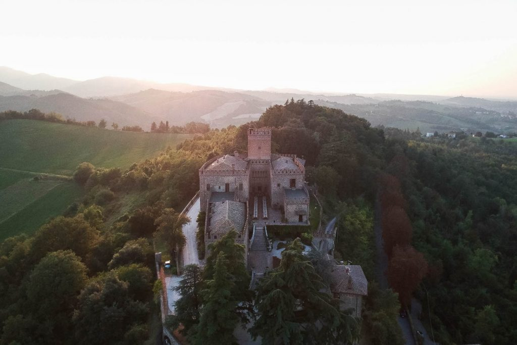 Aerial photo of a stunning castle set on a hill with the golden light of sunset glowing around it. Fine art wedding and drone photography by luxury wedding photographer Francesco Bognin