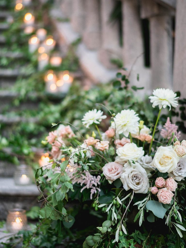 Beautiful candles and flowers in peach, ivory, white, lavender and green running all along a set of stairs leading to a castle in Italy. Fine art weddign photography by luxury wedding photographer Francesco Bognin