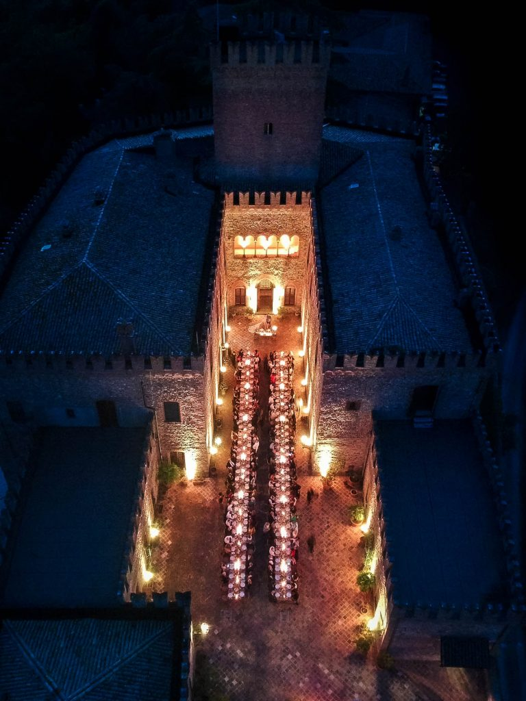 Aerial photo of a stunning castle setting showcasing the dinner setting and glowing with candles that fill it. Fine art wedding and drone photography by luxury wedding photographer Francesco Bognin