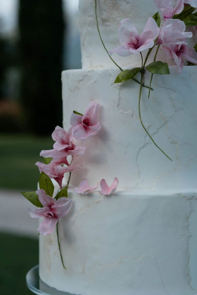 A close up photo of a beautiful three layer wedding cake in textured white, decorated with cherry blossoms shot by luxury wedding photographer Francesco Bognin