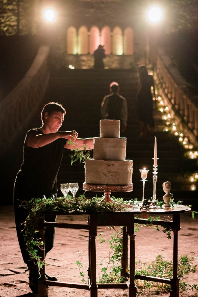 A florist lit by the glow of candles puts the finishing touches on a three level wedding cake as she drapes it in ivy and flowers as the foot of a grand staircase below a castle in Italy. Fine art wedding photography by luxury wedding photographer Francesco Bognin