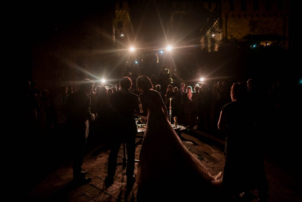 A dark photo with 4 bright lights illuminating a silhouette of a bride and groom from behind as they cut their wedding cake in front of all their guests at the foot of a midevil castle in Italy. Fine art wedding photography by luxury wedding photographer Francesco Bognin