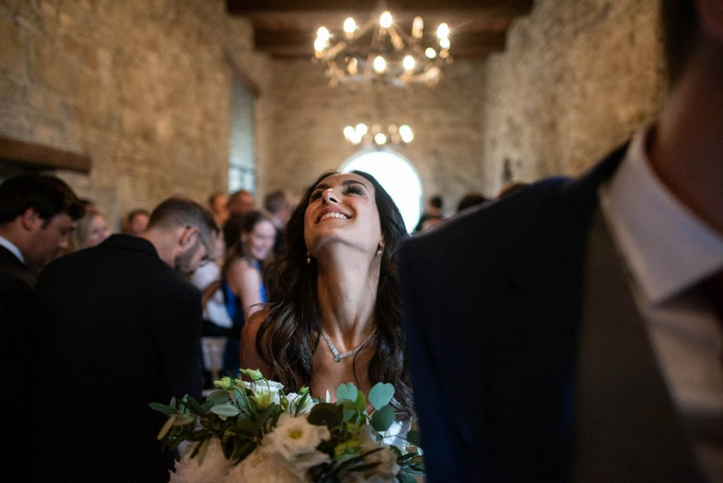 A bride throws her head back in ecstatic joy after her ceremony as she leaves surrounded by her guests and clutching her bouquet. Chandelier lit overhead. Fine art wedding photography by luxury wedding photographer Francesco Bognin