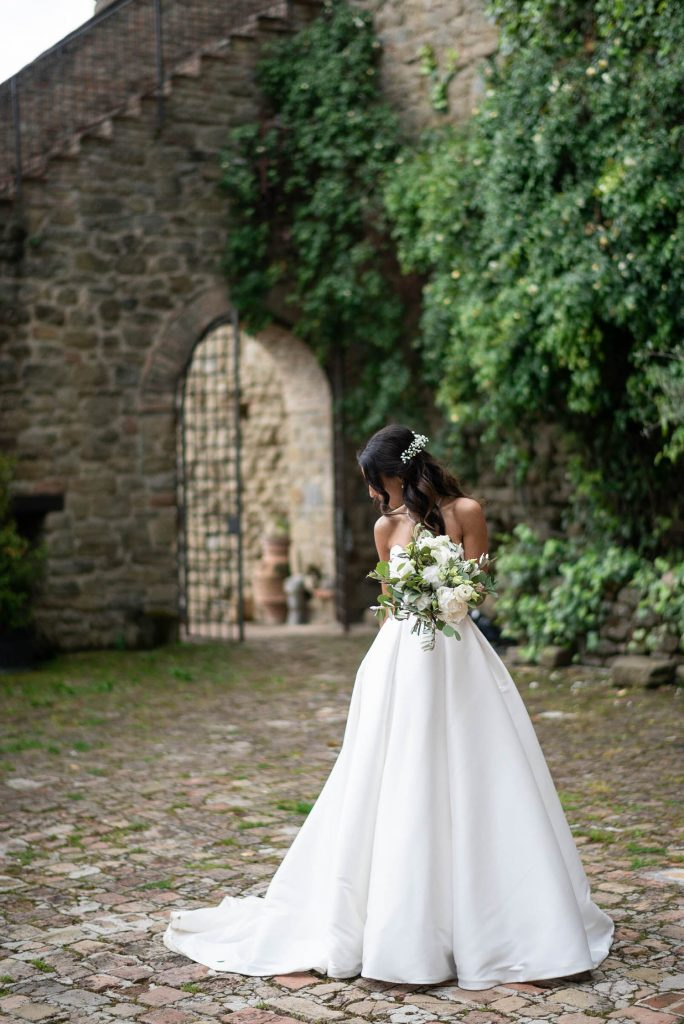 A beautiful bride looks down and to the side as she adjusts her wedding gown holding her bouquet in a stunning Villa garden setting in Italy. Fine art wedding photography by luxury wedding photographer Francesco Bognin