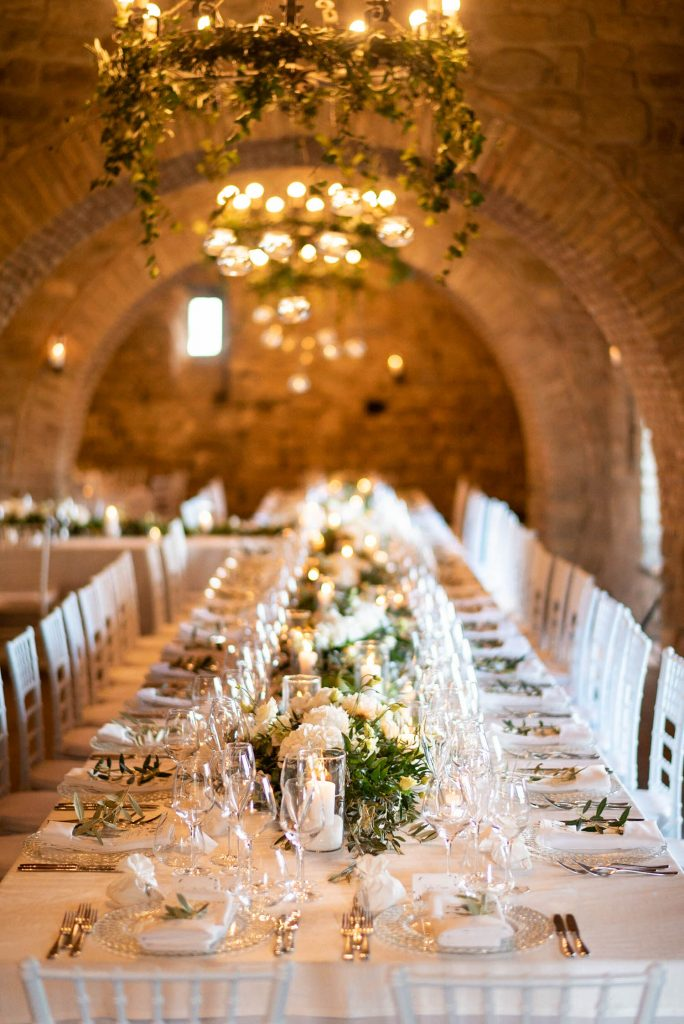 A glowing table setting including a turning imperial table under a sea of glowing candles and dripping Ivy in Italy. Fine art wedding photography by luxury wedding photographer Francesco Bognin