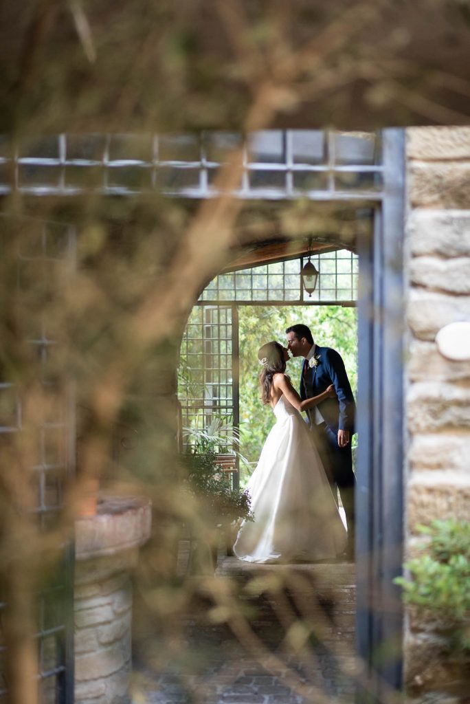 A bride and groom share a kiss as seen through a doorway and from behind a tree in Italy by luxury wedding photographer Francesco Bognin