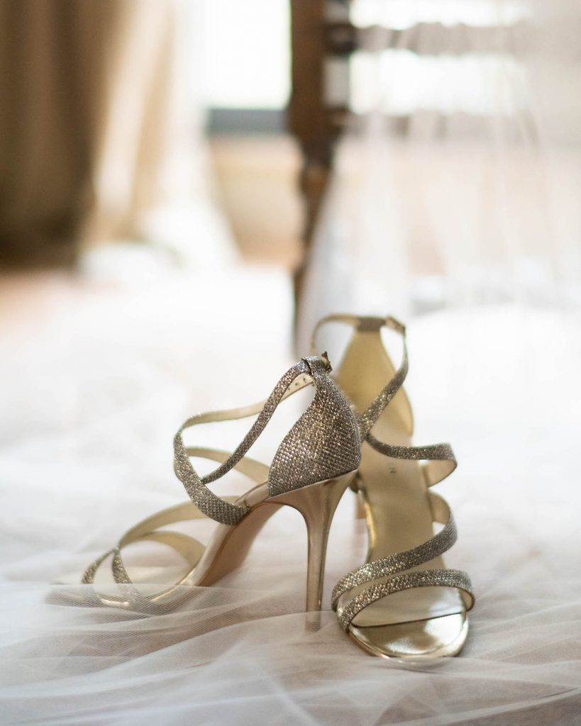 A strapped golden metallic bridal sandal rests on a bridal veil lit by natural light, by luxury wedding photographer Francesco Bognin