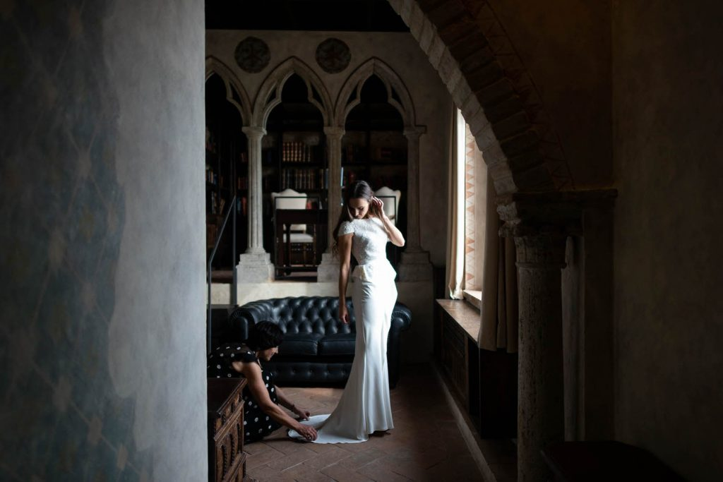 A bride in a dark and ancient villa room stands in the light of a window and looks down as someone adjusts the hem of her dress. By luxury wedding photographer Francesco Bognin