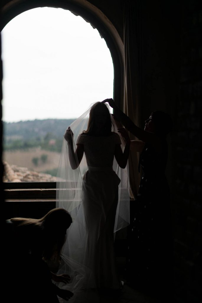 A bride in a dark and ancient villa room stands in the light of a window and looks out a window as someone adjusts her veil and the hem of her dress. By luxury wedding photographer Francesco Bognin