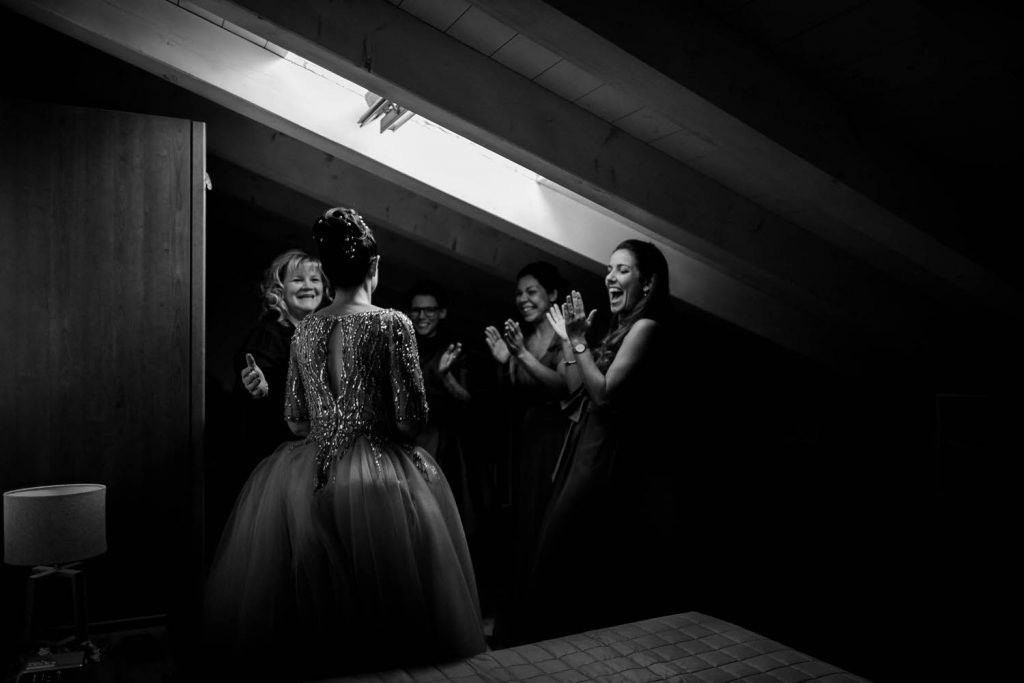 Fine art black and white reportage photo of a bride revealing her wedding gown to her enthusiastic and applauding bridal party and family, lit by the natural light from a skylight in an attic bedroom in Italy, shot by luxury wedding photographer Francesco Bognin