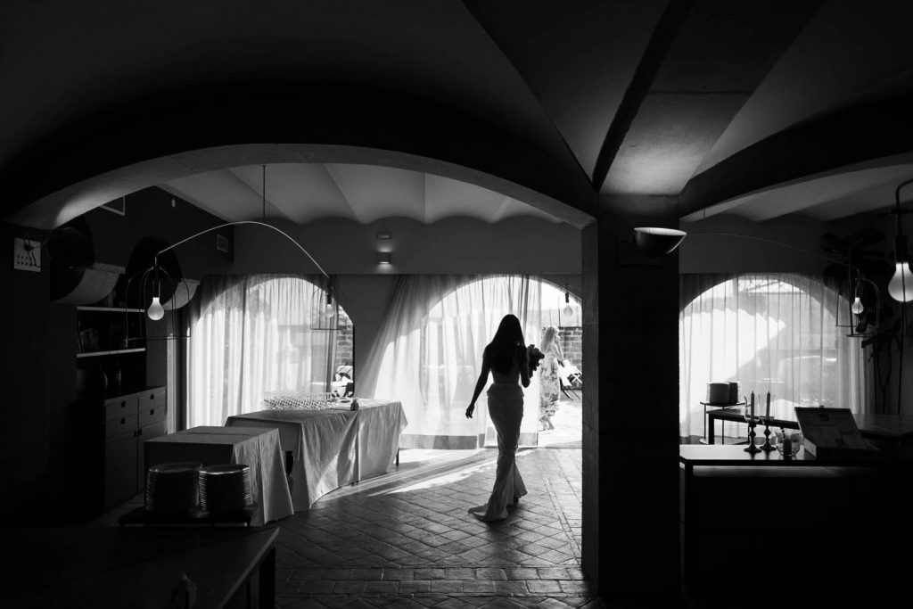Black and white fine art photo of a bride walking in her gown under an arch of an ancient Italian villa, by luxury wedding photographer Francesco Bognin