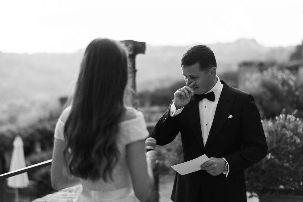 A groom wearing a tuxedo shares his vows and chokes back tears with his hand to his face as seen over the shoulder of his bride in an outdoor ceremony in an ancient Italian Villa, by luxury wedding photographer Francesco Bognin