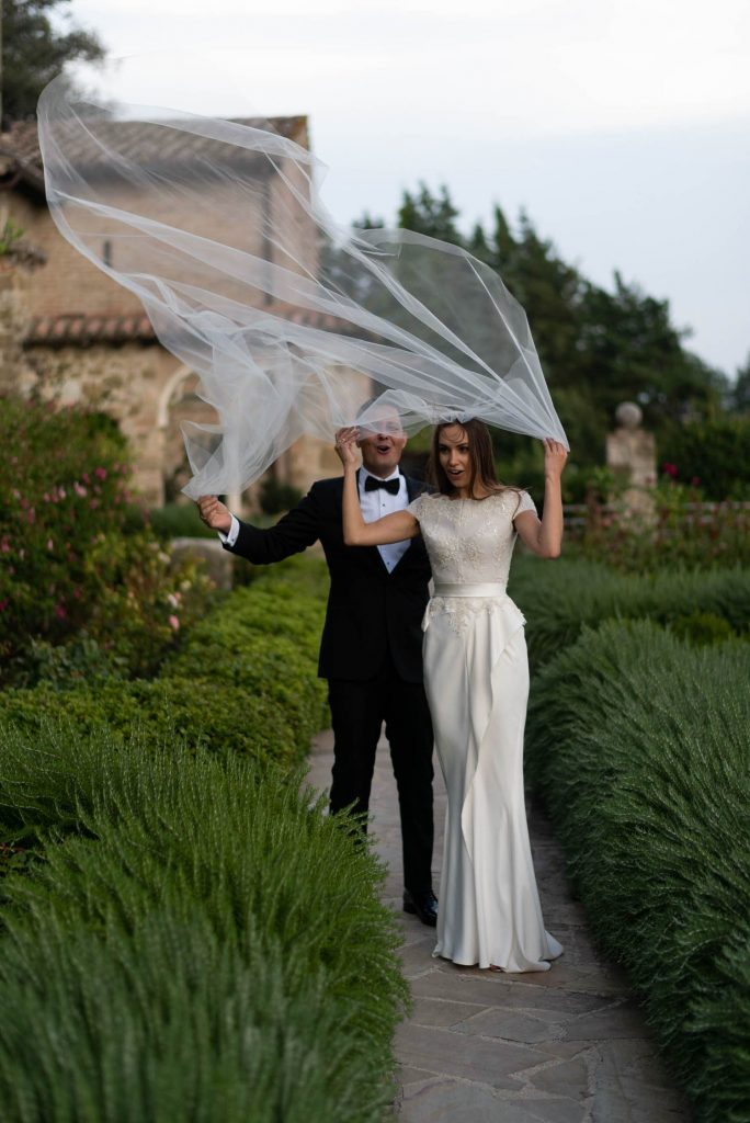A bride and groom walk along a path and are surprised by a gust of wind that sends her veil flying up overhead, by luxury wedding photographer Francesco Bognin