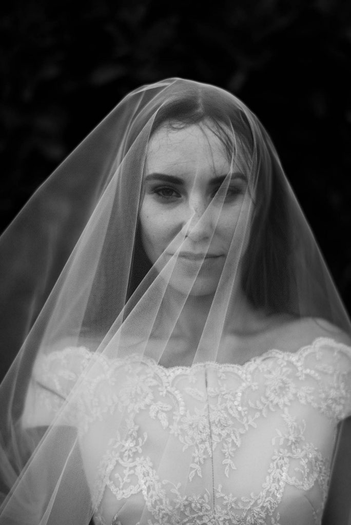 A fine art black and white close up of a bride under her veil wearing a mysterious gaze and a half smile, by luxury wedding photographer Francesco Bognin