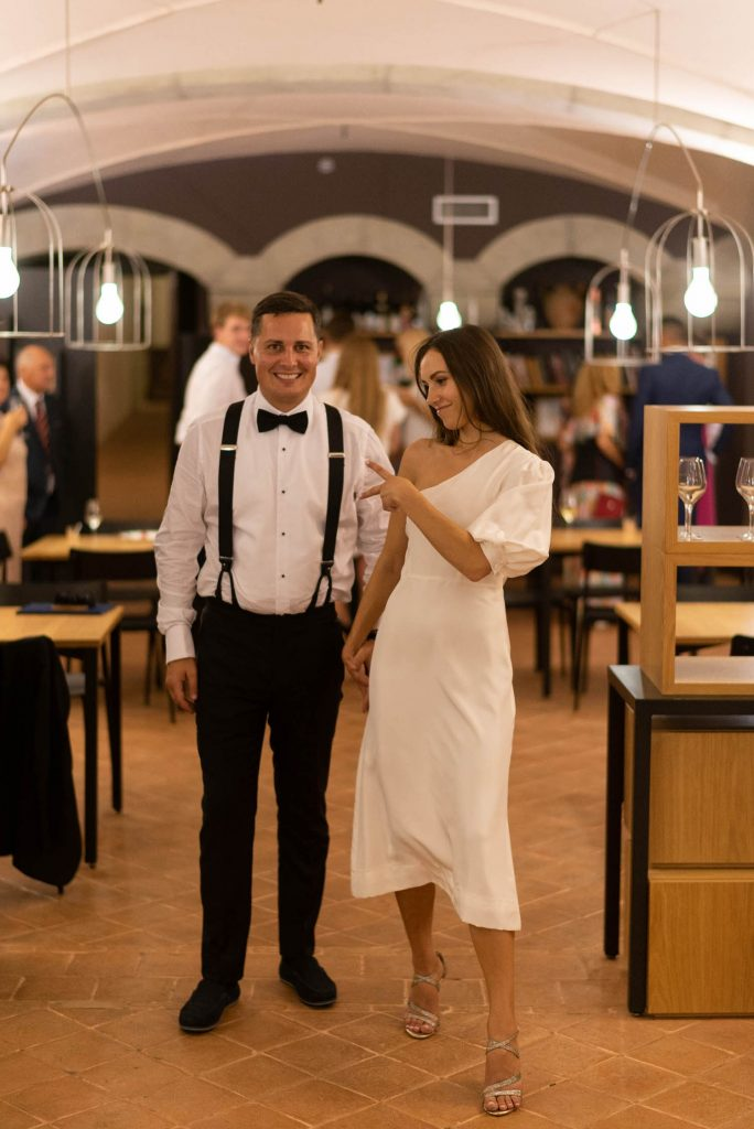 A groom wearing suspenders braces and a bow tie and his bride wearing her second dress walk through their reception venue after their ceremony with smiles and lively postures in Italy, by luxury wedding photographer Francesco Bognin