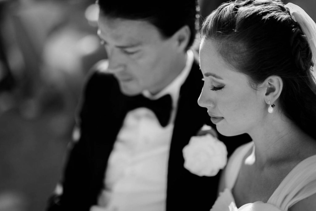 A close up of a groom in a tuxedo and a bride in her gown with eyes closed in a sacred moment during their ceremony on the Emerald Coast of Sardegna, in black and white by luxury wedding photographer Francesco Bognin