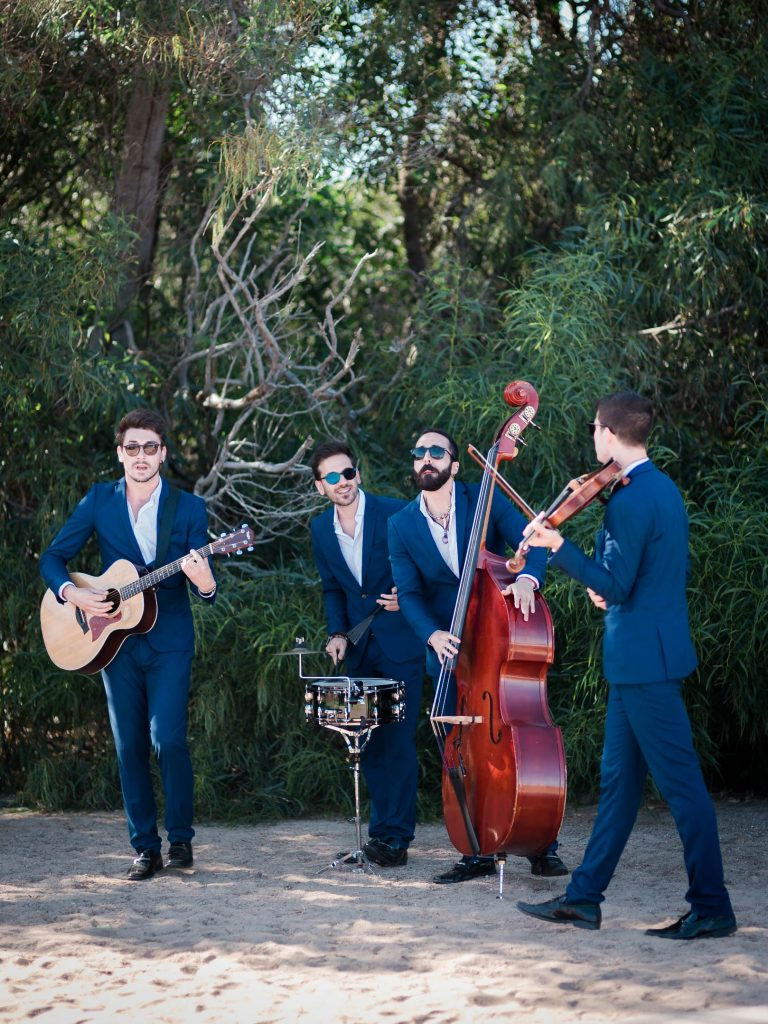 A lively set of four musicians play music on the Emerald coast in Sardegna Italy, by luxury wedding photographer Francesco Bognin