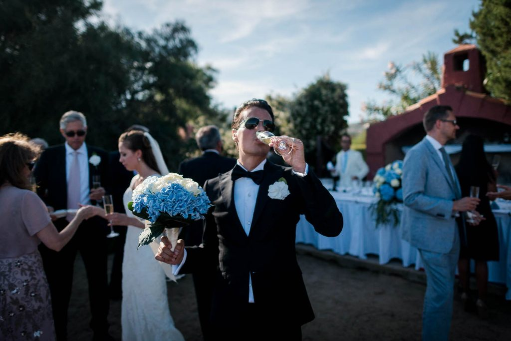 A groom wears a tuxedo and sunglasses as he holds his bride's bouquet and drinks from a glass of wine with his bride in the background on the Emerald coast of Sardinia in Italy, by luxury wedding photographer Francesco Bognin