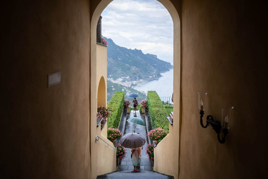 An iconic perspective of a halled staircase leading to a terrace overlooking the sea of the Amalfi Coast in Ravello on a rainy day with guests using umbrellas at a pre-wedding tea ceremony at Belmond Hotel Caruso planned by Brenda Babcock and shot by luxury wedding photographer Francesco Bognin